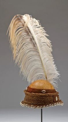 Africa | Boy's headdress; ostrich eggshell, ostrich feather, cowrie shells, beaten bark and fiber | Alur people, Uganda | 20th century
