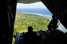 U.S. Air Force Airmen look out the back of a U.S. Air Force C-130 Hercules cargo aircraft during Operation Christmas Drop (OCD), Dec. 12, 2011. The island of Fais is located within the Yap state of the Micronesian islands and is one of the more than 50 islands that will receive care packages this holiday season as part of OCD.