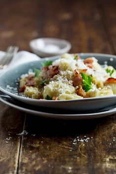 Gnocchi Carbonara:  gnocchi, 250g dry cured, smoked streaky bacon, chopped; 2 cloves garlic, thinly sliced; 4 eggs; 125ml (1/2 cup) cream; 1 cup grated Pecorino cheese; freshly cracked black pepper; salt to taste; large handful chopped Italian parsley.