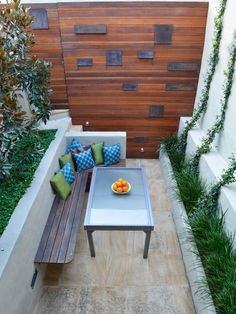 When space is as tight as it is on this 11-foot-wide terrace created by Outhouse Design, attaching benches to a wall is a great way to maximize space. An array of pillows adds color and comfort, and metal art on the back wall adds visual interest to the long, narrow space.