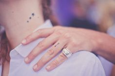 Two small tattoos. First: triple three stars on neck decreasing in size. Second: Arrow on ring finger