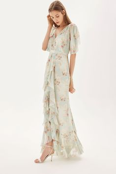 This beautifully made maxi dress comes in a delicate floral print for the feminine girl, finished with pretty details including elegant ruffles, fluted sleeves and covered button detail to the back. With tie fastening to the back, it enhances the silhouette by cinching in at the waist.