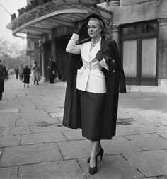 Model is wearing a suit with a nipped waist and double-breasted jacket by British designer Simon Massey, December 1949.