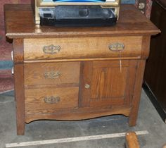 VINTAGE SOLID OAK WASH STAND WITH A BOW FRONT. IT HAS BRASS HARDWARE AND MEASURES 34 X 19 X 28.