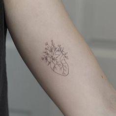 Single needle flower heart tattoo on the left inner arm.