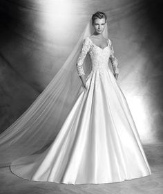 VERSAL style: Princess dress with paillettes, lace, beading and satin. V-neck bodice with paillettes overlaid with tulle and lace and gemstone embroidery appliqués. Sheer sleeves and back with lace and beaded appliqués. Satin skirt with side pockets.