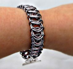 This bracelet is in a vertebrae chain maille weave using Black Pearl outer rings and a light Pink inner ring. The Pink adds a femininity to an
