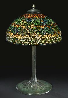 """Tiffany Studios A RARE """"MAPLE LEAF"""" TABLE LAMP with a large """"Tree"""" base shade impressed TIFFANY STUDIOS 1999 base impressed TIFFANY STUDIOS/NEW YORK/553 leaded glass and patinated bronze, circa 1913."""