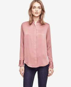 """Delicately pleated ruffles add modern polish to this satiny must-have. Pleated ruffle stand collar with front shirring beneath. Long sleeves with pleated ruffle cuffs and button closure. Hidden button front. Back yoke with box pleat and side pleats. Shirttail hem. 27"""" long."""