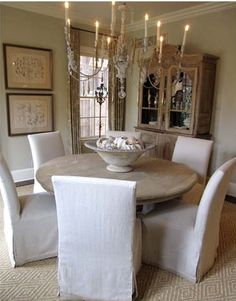 pale and chalky round table with linen slipcovered chairs