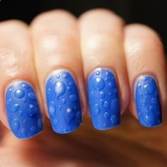 Raindrops falling on nails - base of bright blue cream with blobs of shiny top coat coated with matte top coat over entire nail