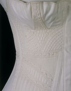 Place of origin: England, Great Britain (made) Date: ca. 1825 - 1835 (made) White cotton corset with silk trapunto work. Busk down centre middle, separate breast double-gussets with trapunto strap in centre of each breast. Corded and quilted work down sides of corset, armholes set quite far back. Laces down the back.