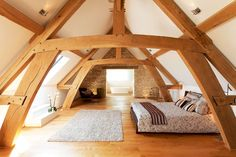 Upper cruck style trusses form an elegant master bedroom. Storey and a half style framing brings an intimate feel to the oak frame carpentry. Oak Frame House, A Frame Cabin, Attic Bedroom Designs, Attic Rooms, Loft Bedrooms, Mezzanine Bedroom, Architecture, My Dream Home, Ideal Home