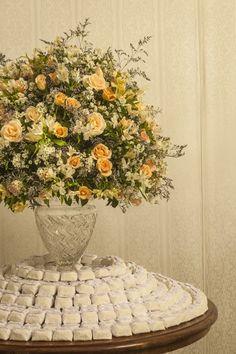 Nessa mesa de docinhos, a decoração fica por conta do lindo arranjo de flores.