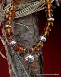 Baltic Amber Beads/Handmade Baltic Amber Bracelet/Hill Tribe Silver Bracelet/Silver Jingle Bell Charm Bracelet/Boho Bracelet/Silver Charm  Beautiful feel to this Baltic Amber beaded bracelet. The Amber beads are genuine from Poland. They feel different then any other beads Ive ever felt, to date. It is said they have anti-inflammatory capabilities and thats why they make teething necklaces with these beads for babies. I also added a really cool Karen Hill Tribe silver...
