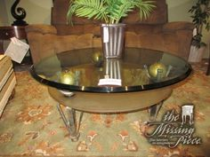 """Glass top coffee table on bronze metal legs with gold orb accents. There is a frosted glass shelf below. 36""""round x 17""""high. Super interesting base!"""