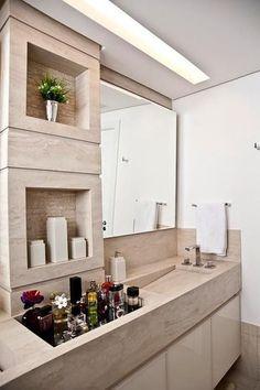 Bancada sob medida possui nichos inteligentes, inclusive um na mesma altura da pia, para acomodar os perfumes. #bancada #bathroom #banheiro #organização #organizar