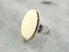 The base of this unique ring is Sterling Silver, a great minimalist piece with a high polish. Weve updated the top of the ring with a disc of polished
