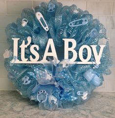 Lovely handmade pastel blue deco mesh wreath - perfect for baby shower, hospital room (in lieu of flowers), front door or babys bedroom door! This wreath is adorned with a hand-painted wood cutout in white announcing Its A Boy, an abundance of blue and white resin baby boy-themed embellishments including baby booties, rattles, baby bracelets, safety pins (small and large), rocking horses, pacifiers and a coordinating handmade wired ribbon bow. All embellishments are shatterproof and… Baby Boy Wreath, Baby Wreaths, Crafts To Sell, Diy And Crafts, Painted Wood, Hand Painted, Baby Deco, Baby Shower Crafts, Baby Bracelet