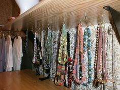 Cup hooks attached on bottom of shelf for hanging necklaces - (my personal idea)