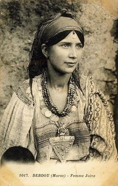 since photo notation in French, maybe she came to Europe via French Morocco ? I like the beads w/ coins. Holy cow ,the huge triangular pendent ! ALady. Some experts have suggested that these may have been oppressed people who were fleeing from onerous conditions. They would have traveled through Central Asia and the Middle East but data indicates only moderate intermingling with local populations that they met.