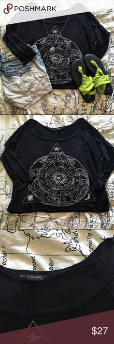 Astrology Top This top is so trendy and fun. It has an astrology triangle graphic on the front in a cream color. The design makes this perfect with a pair of shorts for summer or under a sweater for fall. The 3/4 sleeves make this shirt perfect for any time of the year. It has some small signs of wear, but is in overall amazing condition. There is a small layover detail on the sleeves on the front of the shirt. This top is size L purchased from a local boutique. Rock Rose Classic Tops Tees…