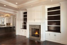I like the contrasting color of the wood at the back of the bookcase in these built in cabinets around fireplace | Great Room with Fireplace and Built-in Cabinets in Saratoga