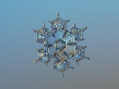 Snowflake macro photo: Flying castle, real snow crystal with beautiful shape and relief glossy surface, sparkling on light brown-blue gradient background
