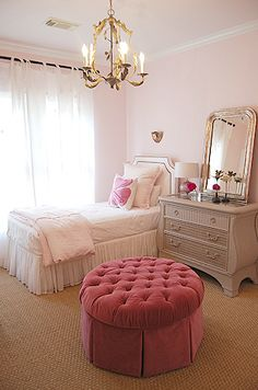 Sally Wheat Interiors    Sweet sophisticated girl's bedroom with pink walls paint color, pink velvet round tufted skirted storage ottoman, jute rug, white twin headboard with nailhead trim, pink duvet & sham, white organza ruffled bed skirt, Louis Phillipe Silver Leaf Mirror and gold tole chandelier.