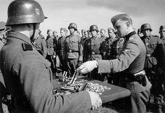 Un SS-Untersturmführer remet la Croix de Fer 2ème classe et la CRoix du Mérite à des membres de la SS-Division Germania