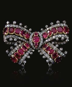 THE ESTATE OF CHRISTIAN, LADY HESKETH Ruby and diamond bow brooch, Mid Century.Designed as a ribbon tied bow set with graduated lines of oval rubies mounted in cut-down collets bordered with lines of old-mine and circular-cut diamonds. Bow Jewelry, Ruby Jewelry, High Jewelry, Jewelry Design, Jewellery, Victorian Jewelry, Antique Jewelry, Vintage Jewelry, Diamond Bows