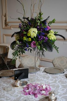 Tall centerpiece in martini vase with shades of purple and greens.