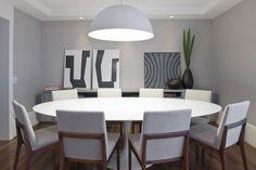 Sala de jantar com mesa oval branca Saarinen + cadeiras de madeira e tecido claro + pendente redondo branco + aparador de laca com quadros apoiados. Gosto muito da cor cinza das paredes contrastando com o rodapé branco mais alto.