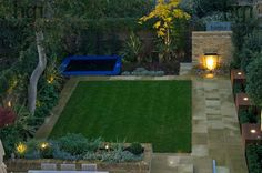 Harpur Garden Images Ltd :: gilday9 Contemporary modern minimal stylish family urban town garden with lighting lawn brick wall water feature lip cascade waterfall light lit uplight path paving edged raised bed border child game play toy sunken trampoline overview from above autumn October Designed by Justin Greer for Mr and Mrs Gilday Wandsworth, London UK Marcus Harpur Contemporary, modern, minimal, stylish, family, urban, town, garden, lighting, lawn, brick, wall, water, feature, lip…