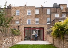 Beams supporting a rear extension to this Victorian house in London are painted vivid red to create a bold contrast with the property's traditional interior