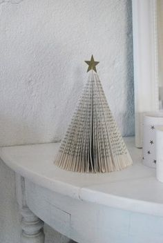 Create an arrangement of Christmas trees made from old books with simple sparkling stars on top.