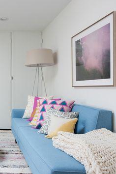 A light blue couch with fun patterned throw pillows gives this living room a midcentury, bohemian style.