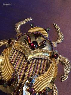 Christmas Beetle. Goldwork and stumpwork. Gold threads, check purl, plate, garnets, beads. Embroidery by Larissa Borodich