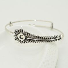 Unique gift idea: Phoenix Feather Bangle Bracelet. This silver bangle bracelet is awesome for women who loves fantasy jewelry. Great gift for your friend, girlfriend, mom and for that best friend of yours who's just a harry potter junkie!