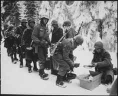 Chow is served to American Infantrymen on their way to La Roche, Belgium. 347th Infantry Regiment, 13 janvier 1945