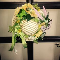 A straw hat wreath. Great for spring, summer. It is full with flowers, birds, butterflies. Come check it out. It is an unsual wreath or can be used as table decor.