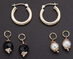 A set of white gold hoop earrings with two pairs of charms: the first featuring black onyx faceted beads, and the second round cultured white pearls, each set in  14k gold.