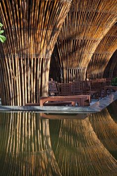 """Green Steel of the 21st Century"" -  Fifteen conical bamboo columns support the roof of this waterside cafe designed by Vo Trong Nghia Architects 