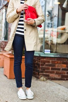 Cute spring outfit. Trench, stripes, skinny jeans, & sneakers. Red statement clutch.