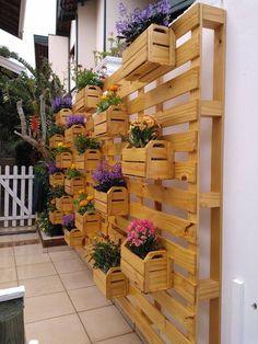 Jardim vertical feito com paletes e caixotes de madeira.