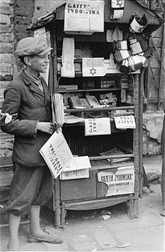 A teenage vendor sells newspapers and armbands in the Warsaw ghetto