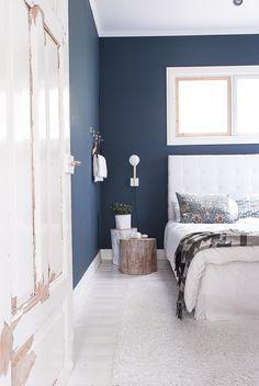 Vierashuoneen intensiivinen sinisen sävy on Farrow & Ballin mattapintainen Hague Blue. Yöpöytinä ovat pölkyt, jotka Tuija on pintakäsitellyt.