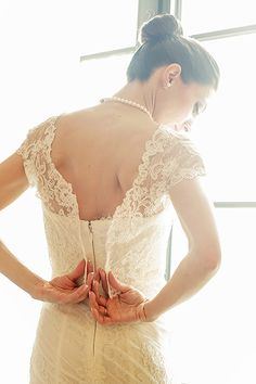 The back of a @m_lhuillier wedding dress with a lace overlay | Brides.com