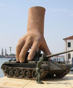This is Not a Game, Sculpture of Giant Hands Playing with Life-Sized Tank and Toy Soldiers