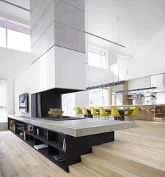 Huge and very modern living area on two levels, with the kitchen and the dining room on a level separated by a very modern grey and white fireplace leading to the living room | Très grande pièce à vivre avec sur un niveau la cuisine et la salle à manger, la cheminée au style moderne et aux couleurs blanc et gris sépare le salon du reste de la pièce.